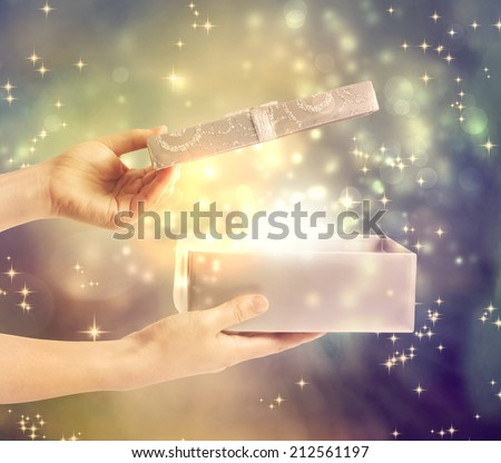 A magical glowing present box being opened  - stock photo