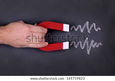 A magnet with zig zag lines showing attraction on a chalk board - stock photo