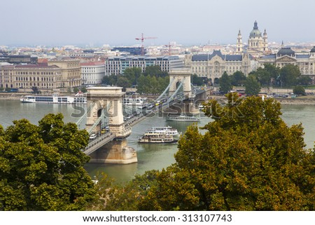 A magnificent view from Castle Hill in Budapest.  The view includes the sights of the Chain Bridge spanning over the River Danube and St. Stephens Basilica in the background. - stock photo