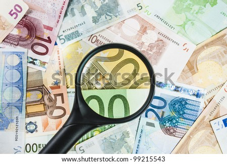 A magnifying glass on different euro bills as a background - stock photo