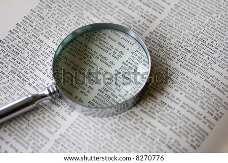 A magnifying glass sits on an old dictionary in natural lighting - stock photo