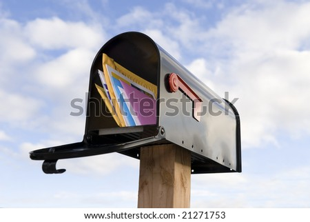 A mailbox full of mail against a blue and puffy white cloud sky - stock photo