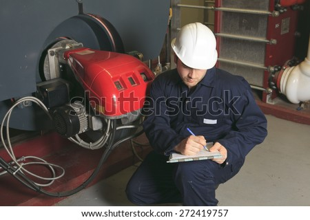 A maintenance engineer checking technical data of heating system equipment in a boiler room - stock photo