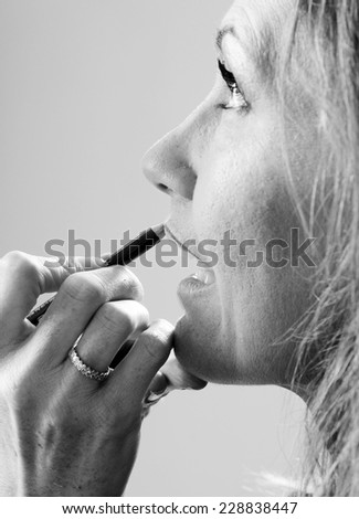 a make up artist hand close up applying lips line with a pencil in black and white - stock photo