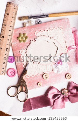 A making scrapbooking postcard with tolls and decorations on the table - stock photo