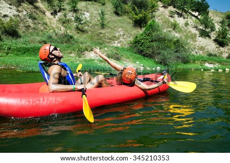 A male and female in a red inflatable canoe celebrating reaching calm waters of a river. - stock photo