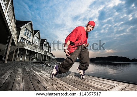 A male breakdancer posing on the pier by the sea - stock photo