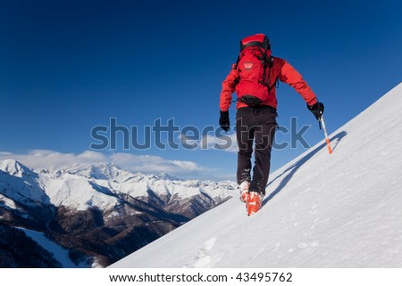 A male climber , dressed in red, climbs down a snowy slope. Winter clear sky day. In background the Monte Rosa massif, Italy, Europe. - stock photo