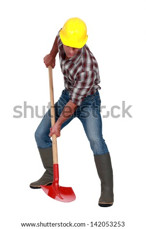 A male construction worker using a shovel. - stock photo