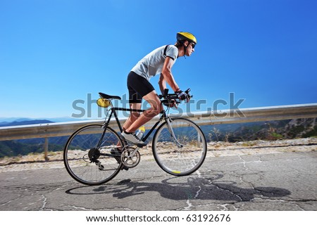 A male cyclist riding a bike uphill along a road; clear summer day - stock photo