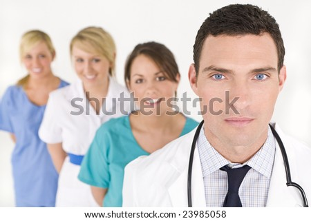 A male doctor with his team of colleagues out of focus behind him. - stock photo