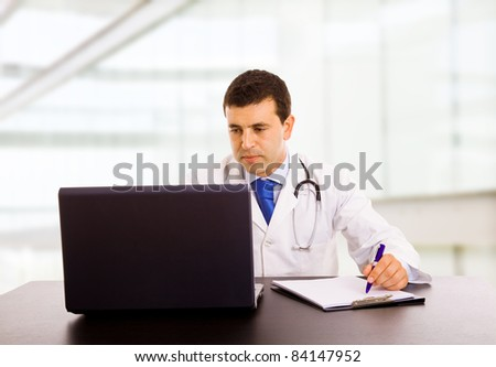 A male doctor working at the desk in hospital office - stock photo