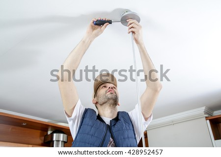 A male electrician fixing light on the ceiling with screwdriver. Close-up. - stock photo