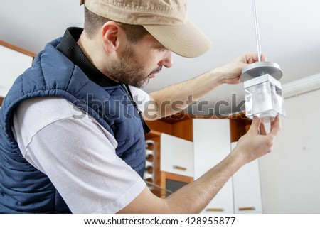 A male electrician fixing light on the ceiling. Worker changing a light bulb in the kitchen. Close-up. - stock photo