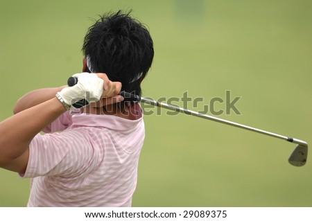 A male golfer hits a ball and is in his back swing. - stock photo