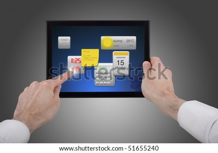 a male hand holding a touchpad pc, one finger touches the screen and uses little programmes - stock photo