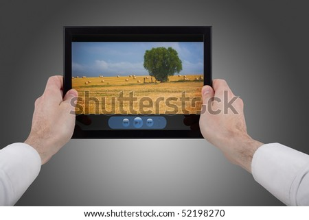a male hand holding a touchpad pc showing a movie, isolated on white - stock photo