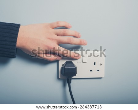 A male hand is pushing a switch on a wall socket - stock photo
