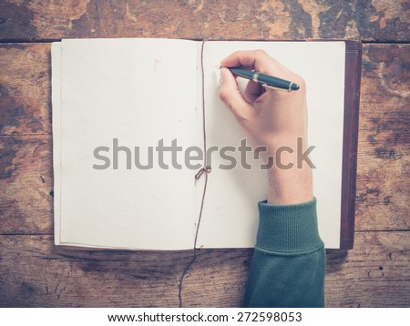 A male hand is writing in a big notepad on a wooden table - stock photo