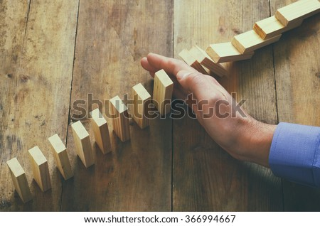 a male hand stopping the domino effect. retro style image executive and risk control concept  - stock photo