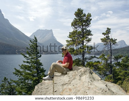 A male hiker rests on a large boulder while enjoying a healthy snack by a beautiful mountain lake. - stock photo