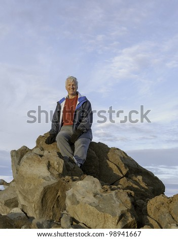 A male hiker rests on a large rocky outcropping overlooking the beautiful valley below. - stock photo