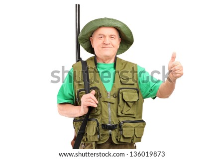 A male hunter with shotgun giving a thumb up isolated on white background - stock photo