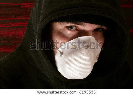 A male lurking in the shadows wearing a mask. - stock photo