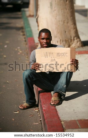 "a male model holds a cardboard sign that reads ""will model for food"" - stock photo"
