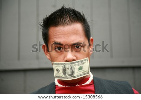 a male model wears a one hundred dollar bill taped over his mouth in protest to represent being silenced by the us economy - stock photo