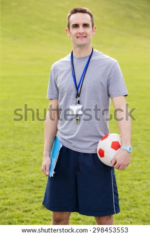 A male sports teacher stands outdoors in a field, he is holding a clipboard and football - stock photo