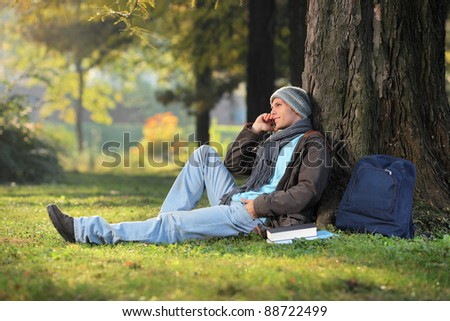 A male student talking on a phone seated on a grass in the city park - stock photo