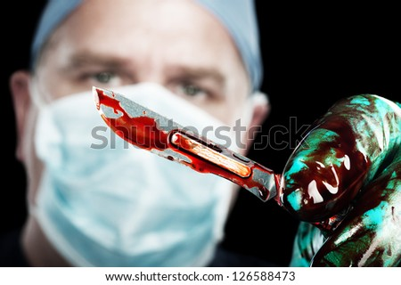 A male surgeon holds up a sharp, bloody scalpel during surgery - stock photo