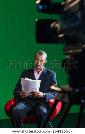 A male television presenter sits alone, reading through scripts before a recording in a green screen TV studio - stock photo