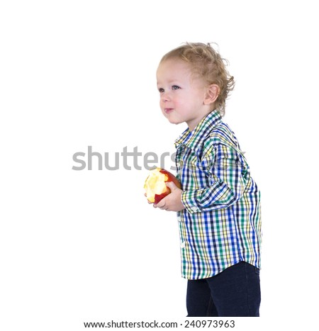 A male toddler holds an apple and has a bite in his mouth. Isolated on white.  - stock photo