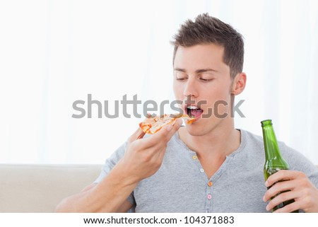 A man about to eat some pizza as he holds some beer in his other hand - stock photo