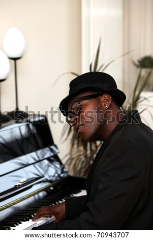 a man - Afro-Africans with hat sitting at the piano and plays - stock photo