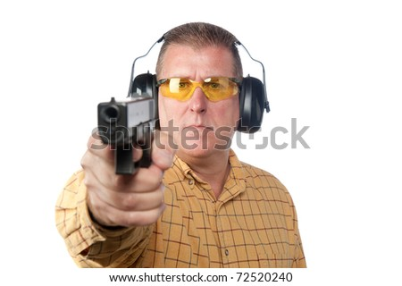 A man aims a handgun while wearing proper safety equipment such as safety glasses and hearing protection. - stock photo