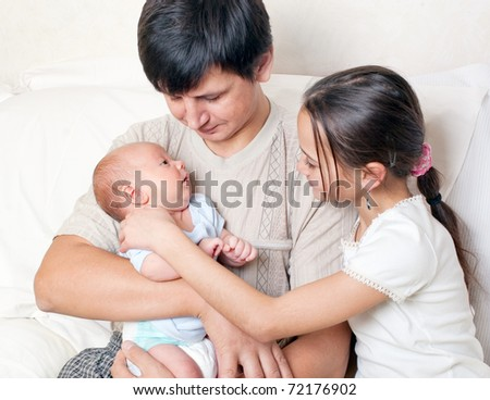 A man and a girl with a newborn baby - stock photo