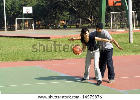 A man and a woman are playing on a park basketball court.  The woman is dribbling the basketball and blocking the man.  They are looking away from the camera.  Horizontally framed shot. - stock photo