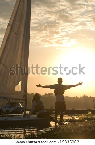 A man and a woman are standing against the sunset on their sailboat. Vertically framed shot. - stock photo