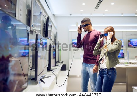 A man and a woman shopping for a 3D TV. - stock photo