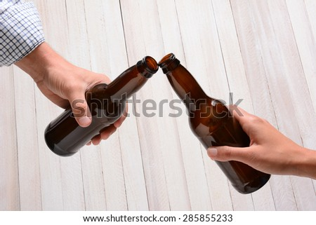 A man and a woman toasting with beer bottles. They are clinking the bottle tops over a rustic wood background. - stock photo
