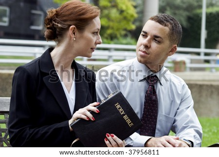 A man and a woman who are discussing what they just read in the Holy Bible, perhaps while on break from work. - stock photo