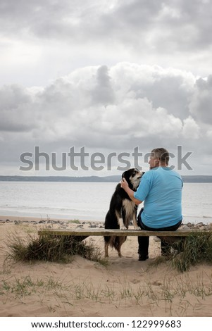 A man and his dog sitting on a bench on a beach - stock photo