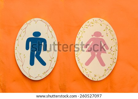 A man and lady toilet sign on orange background - stock photo