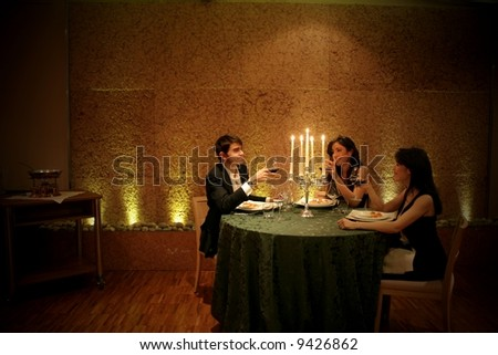 a man and two woman at restaurant - stock photo