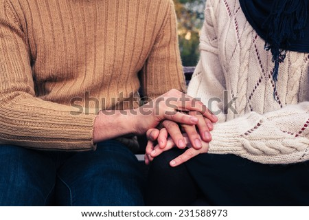 A man and woman are holding hands and comforting each other in a park - stock photo