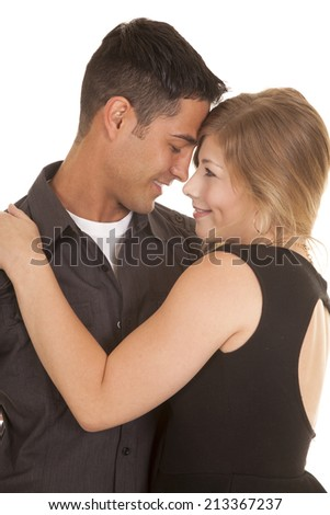 A man and woman cuddling close together with smiles on their lips. - stock photo