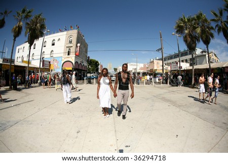 a man and woman walk hand in hand in Venice Beach California. Shot through a Fish Eye lens for a unique effect - stock photo